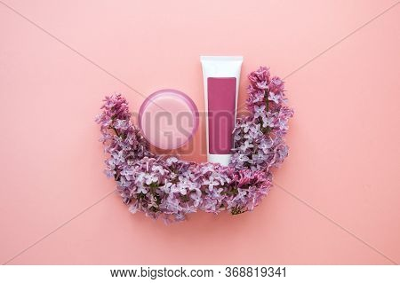Jar And Tube With Cosmetic Cream In Lilac Color And A Sprig Of Lilac On A Pink Background, Cosmetics