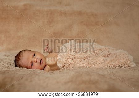 Newborn Baby Sleeping, Resting On Her Own Hands And Elbows, On Brown Background