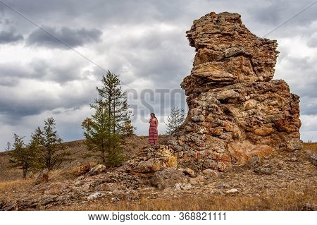A Girl Stands Next To A Stone Outlier Against The Sky. Old Dilapidated Stones. A Few Trees Nearby. C
