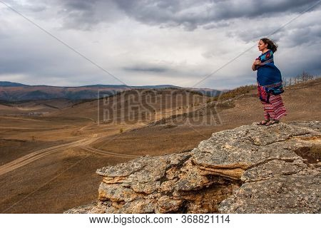 A Girl Stands On A Stone Block In The Steppe. Model In A Dress And Scarf. Below Are Steppe Roads And