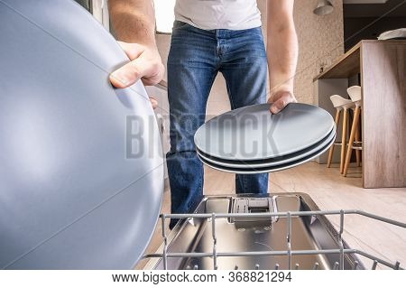 Man Taking Clean Plates From Dishwasher. View From Dishwasher. Housekeeping.