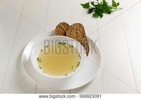Fresh Bouillon In A White Plate With Herbs And Croutons Of Grain Bread On A White Background. Hot So