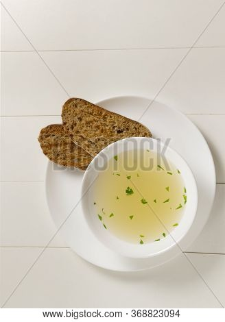 Fresh Bouillon In A White Plate With Finely Chopped Greens And Croutons On A White Background. Hot S