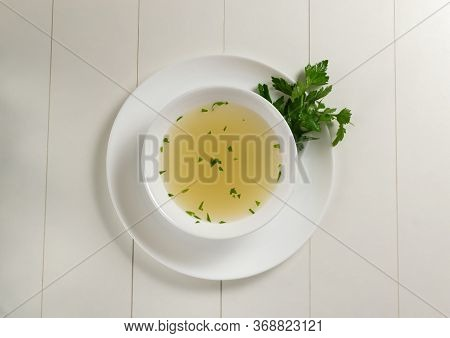 Fresh Bouillon In A White Plate With Finely Chopped Herbs On A White Background. Hot Soup Made From