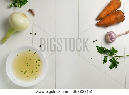 Fresh Bouillon In A White Plate With Finely Chopped Herbs With Ingredients On A White Background. Ho