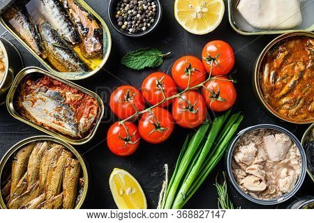 Mix Of Canned Preserves Food In Cans With Fresh Organic Bio Ingredients Tomatoe Herbs Lemon On The B