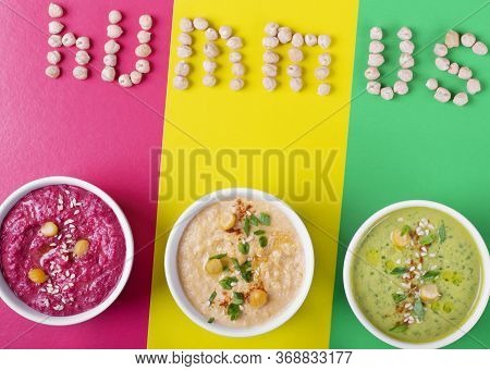 Multicolored Hummus Against The Geometric Background. The Word Hummus Is Written Above The Three Bow