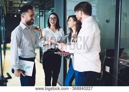 Enthusiastic Office Workers Having Conversation In Modern Office