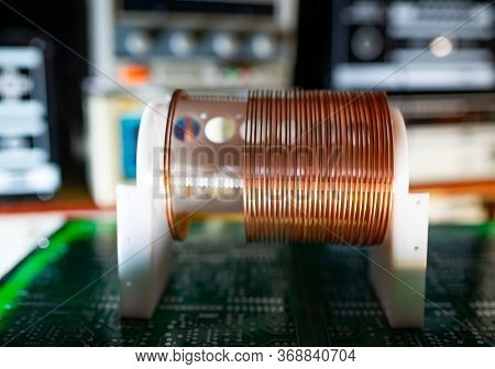 Close-up Large And Small Coils With Copper Wire Stand On A Green Microcircuit At A Factory Of Classi