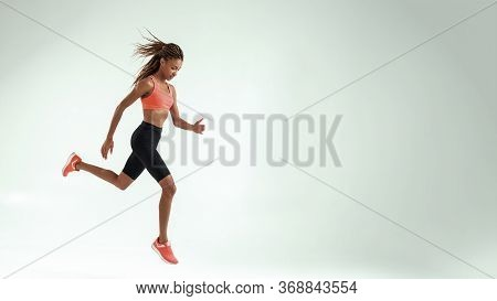 No Limits. Full Length Of Young African Woman With Perfect Body In Sports Clothing Jumping Against G