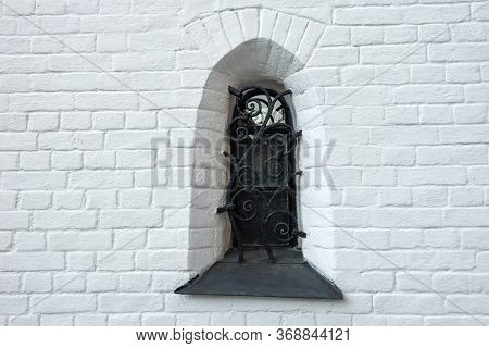 Window In An Old Brick House Protected By Forged Bars