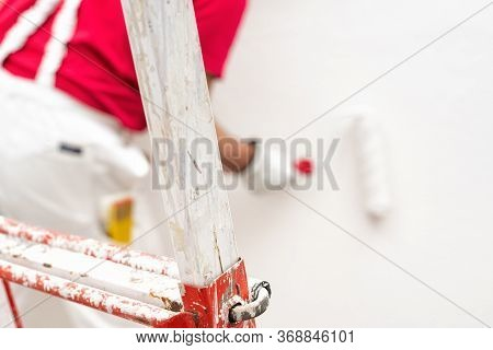 Caucasian House Painter Worker In White Work Overalls And With Protective Gloves, Painting The Wall