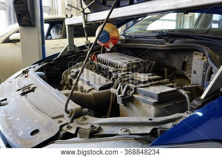 Car In Service With An Open Hood. In The Photo, The Top Of The Engine, The Battery. Service, Repair,