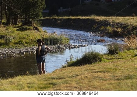 A Woman Relaxes By The River
