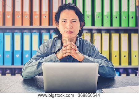 Asian Businessman Using Laptop Sitting On Desk Look At Camera Determination, Willpower Stay Focused