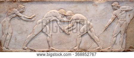 Ancient Bas-relief On Grave Stele In Kerameikos With Scene From Palaestra - Wrestlers In Action. On
