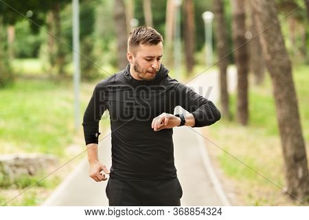 Morning Routine Concept. Portrait Of Handsome Guy Running In Parkland, Checking Heart Rate On His Sm