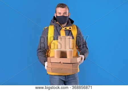 Young Caucasian Food Delivery Man In Protective Black Mask And Gloves Against Virus And Bacteria Is