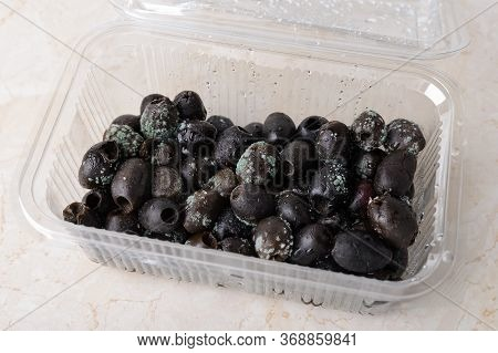 Spoiled Olives With White Green Mold In A Plastic Food Container On A Kitchen Table. Mold Fungus On