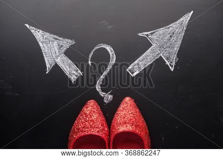 Shoes And Arrows Pointing In Different Directions On Asphalt Floor,