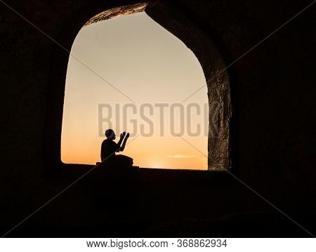 A Realistic Arabian Interior Miniature With Window And Columns. Silhouette Of Muslim Praying On Carp