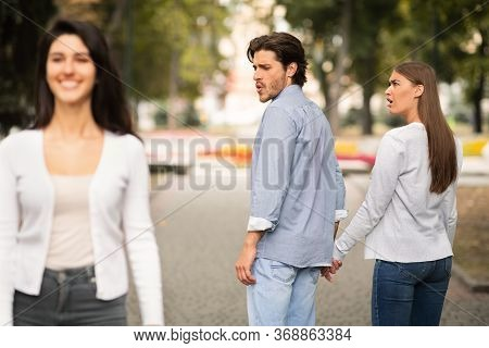 Boyfriend Looking At Other Girl Walking With His Irritated Girlfriend Outdoor In Park. Relationship