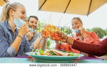 Friends Drinking Coktail And Eating Snack Tapas In A Restaurant Bar Outside In Summer Days With Face
