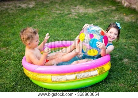 Toy For Children Games. Children Playing With Inflatable Rubber Beach Ball. In Water Pool. Summer Ho