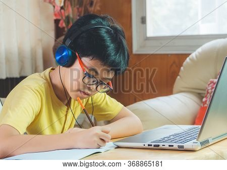 The Boy Wearing Headphones Sitting At The Table With Internet Chat Skype Teacher Prepare For Exam An