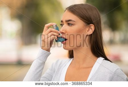Asthma Concept. Girl Having Asthmatic Attack Using Inhaler Feeling Bad Walking Outside In City.