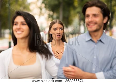 Cheating Boyfriend. Desperate Girl Meeting Her Man Dating With Other Woman Walking Outside In Park.