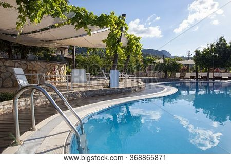 Backyard Of A Hotel With A Swimming Pool And Great Mountain View. Pool Ladder.