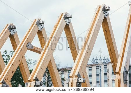 Wooden Rafters Of Unfinished Roof Against The Background Of The City And White Sky. The Concept Of B