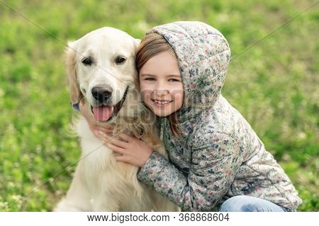 Portrait of pretty little girl embracing cute dog on blooming spring flowers background