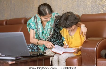 Young Mother Teaching Her Child While Working On Laptop - Concept Of People Lifestyles And Technolog