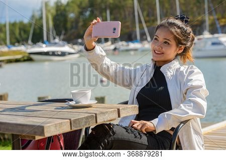 Happy Young Beautiful Asian Tourist Woman Taking Selfie At Restaurant By The Pier