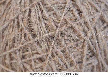 Ball Of Natural Unpainted Wool Handmade Closeup. Light Brown Or Beige Background Or Wallpaper. Handi