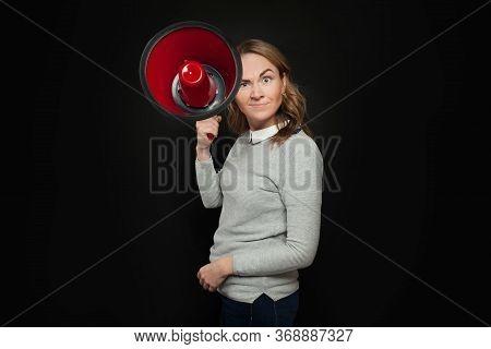 Girl Holding Big Red Bullhorn On Black Background. Woman With Loudspeaker Megaphone