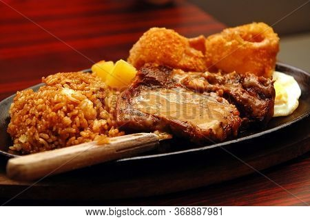 Beef Steak With Onion Rings And Rice In Sizzling Plate
