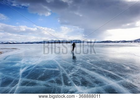 Lake Baikal, Russia - March 13, 2020: Man Ice-skating On The Frozen Lake Baikal With Snow Covered Mo