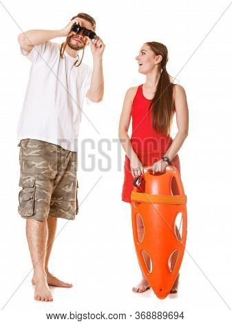 Lifeguards With Rescue Buoy Tube Nad Binoculars. Man And Woman Supervising Swimming Pool. Accident P