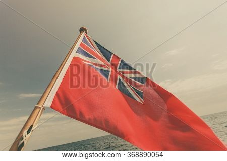 The Uk Red Ensign The British Maritime Flag Flown From Yacht Sail Boat, Blue Sky And Baltic Sea. Sum