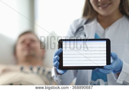 Doctor In Clinic Shows Patients Cardiogram Tablet. Examination And Diagnosis Heart, Cardiogram. Card