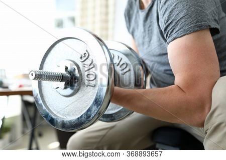 Guy Sits At Home And Lifts Heavy Metal Dumbbells. Sports Equipment Effective For Strength Training.