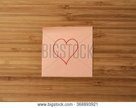 A Paper Sticker Pasted On A Wooden Surface With The Image Of The Heart Symbol