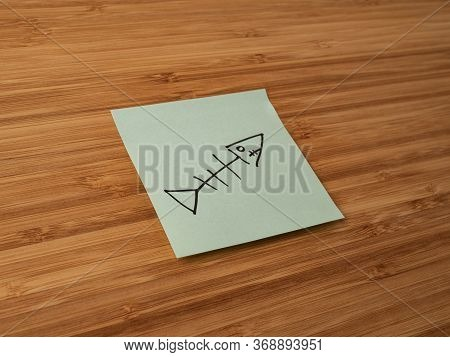 A Paper Sticker Pasted On A Wooden Surface With The Image Of The Fish Skeleton Symbol
