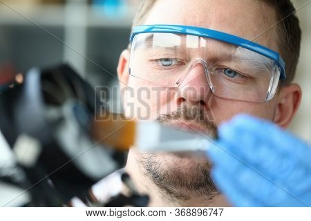 Male Repairman Looks At Computer Detail Processor. Masked Man Repairs And Dusts Computer Part. Free