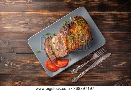 Homemade Baked Pork Meat With Vegetables And On A Serving Board On A Wooden Table. Top View. Copy Sp