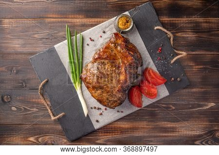 Homemade Baked Piece Of Meat With Vegetables And On A Serving Board On A Wooden Table. Top View. Cop