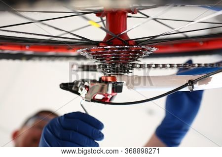 Gloved Man Repairing Bicycle Wheel With House Key. Repair Mechanical Part Bicycle. Diagnostics And A